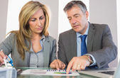 Two frowning business people pointing at a graphic — Stock Photo