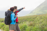 Couple of hikers with backpacks pointing at mountain — Stok fotoğraf