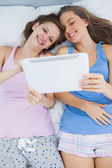 Smiling girls lying in bed holding tablet — Stock Photo