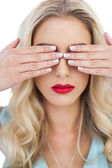 Blonde model in blue dress hidding her eyes with her hands — Stock Photo