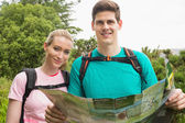 Athletic couple holding map on a hike — 图库照片