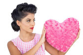 Charming black hair model holding a pink heart shaped pillow — Stock Photo