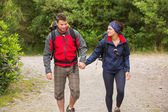 Smiling couple going on a hike together holding hands — Stock Photo