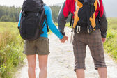 Hikers with backpacks holding hands — Stockfoto
