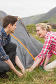 Smiling couple pitching their tent together — Stock Photo