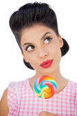 Wondering black hair model holding a colored lollipop — Stock Photo