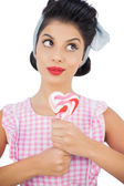 Pensive black hair model holding a heart shaped lollipop — Stock Photo