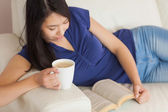 Happy young asian woman lying on the sofa reading a book holding her coffee — Stock Photo