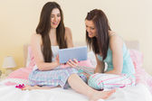 Girls in pajamas talking on bed using a tablet — Stock Photo