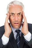 Surprised businessman looking at camera holding his temples — Stock Photo