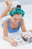Smiling girl in hair rollers lying on bed — Stock Photo