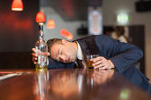 Unmoving businessman holding whiskey glass lying on a counter — Stock Photo