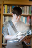 Serious student analysing graphs on his digital tablet — Stock Photo