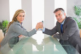 Two serious businesspeople having an arm wrestling sitting around a table — Stock Photo