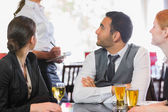 Business people talking to the waiter — Stock Photo