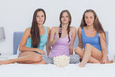 Girls sitting on bed at sleepover — Stock Photo
