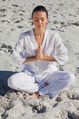 Concentrated woman practicing yoga on the beach — Stock Photo