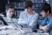 Serious students working on their digital tablet pc — Stock Photo