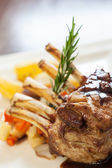Delicious rack of lamb dish with rosemary sprig — Stock Photo