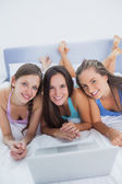 Girls on bed with laptop — Stock Photo