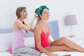 Girls sitting in bed one wearing hair rollers — Stock Photo
