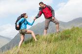 Atractivo excursionista ayudando a su novia cuesta arriba — Foto de Stock