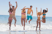 Happy friends jumping on the beach — Stock Photo