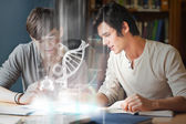 Smiling college students analysing dna on digital interface — Stock Photo