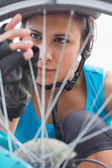 Focused woman adjusting her spokes on bike wheel — Stock Photo
