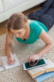 Focused young woman lying on floor using tablet to do her assignment — Stock Photo