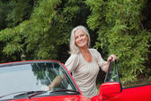 Cheerful mature woman getting off her convertible — Stock Photo