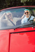 Mature couple in red cabriolet smiling at camera — Stock Photo