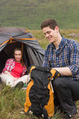 Man packing backpack while girlfriend sits in tent — Stok fotoğraf