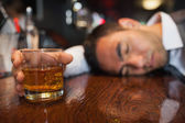 Drunk businessman with whiskey in his hand lying on a counter — Stock Photo