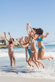 Side view of leaping friends at the beach — Stock Photo