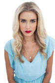 Severe blonde model in blue dress looking at camera — Stock Photo