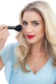 Amused blonde model in blue dress applying make up — Stock Photo