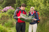 Sporty couple on a hike looking at map — Stock Photo