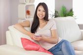 Pretty asian girl using her smartphone on the couch smiling at camera — Stock Photo
