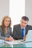 Two focused business people looking at camera trying to understand figures — Stock Photo