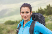Attractive female hiker with backpack smiling at camera — Stock Photo