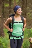 Mulher radiante de pé em uma floresta em uma caminhada — Foto Stock