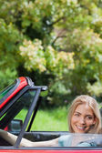 Happy blonde woman driving red cabriolet — Stock Photo