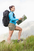 Attractive hiker with backpack walking uphill holding a map — Stok fotoğraf