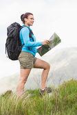 Escursionista attraente con zaino, camminando in salita tenendo una mappa — Foto Stock