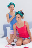 Girls in hair rollers and pajamas chatting — Stock Photo