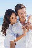 Gülümseyen çift sahilde birbirlerine kucaklayan — Stok fotoğraf