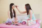 Smiling girl giving her friend a makeover at sleepover — Stok fotoğraf