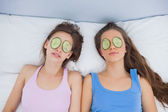Friends relaxing in bed with cucumber on eyes — Stock Photo