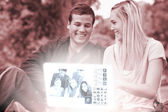 Cheerful young couple watching photos together on digital interface — Stock Photo